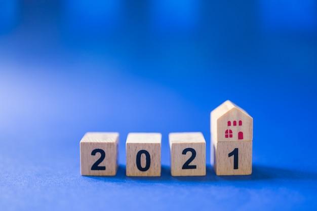 Primo piano del mini giocattolo della casa di legno sulla parte superiore del blocco numerico di legno 2021 su fondo blu