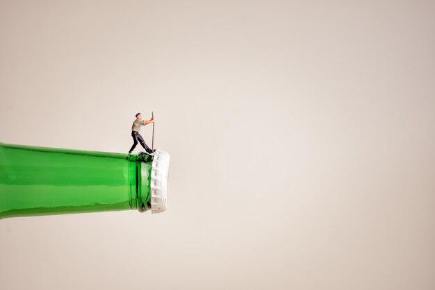 Primo piano di un lavoratore in miniatura che apre una bottiglia