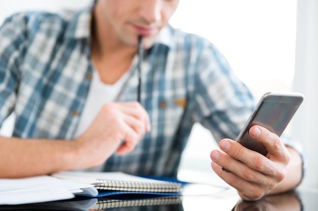 Primo piano del telefono cellulare e del blocco note usati da un uomo premuroso in camicia a quadri al tavolo