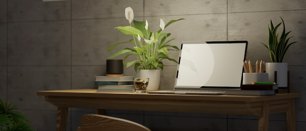 Primo piano moderna installazione sul posto di lavoro del computer loft con cancelleria per laptop e decorazioni in muro di cemento 3d