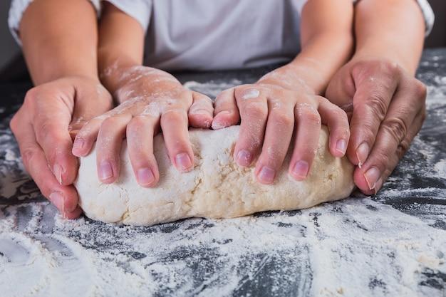 Primo piano delle mani della madre e delle figlie che impastano insieme