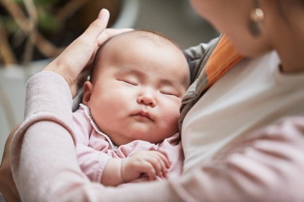 Primo piano della madre che tiene in braccio il suo bambino addormentato cullandola e accarezzandola sulla testa