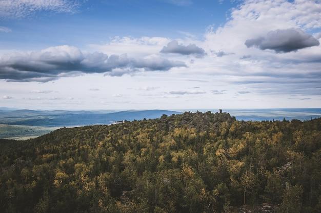 Scene di montagne del primo piano nel parco nazionale kachkanar, russia, europa. tempo nuvoloso, cielo di colore blu drammatico, alberi verdi lontani