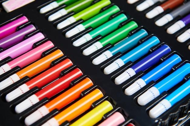 Primo piano dei pennarelli multicolori nella scatola nera. strumenti per il disegno e l'istruzione