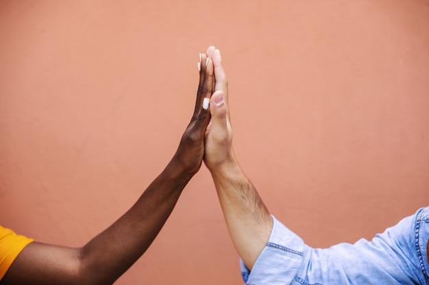Primo piano delle coppie multiculturali che danno il cinque.