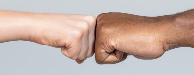 Primo piano di amici multiculturali che si danno il pugno a vicenda mani maschili e femminili di razza afroamericana nera che danno un pugno, diversità multirazziale, concetto di immigrazione