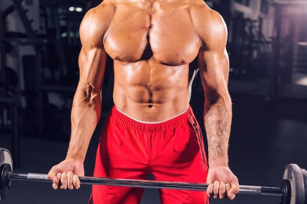 Primo piano di un giovane muscoloso sollevamento pesi sulla parete scura