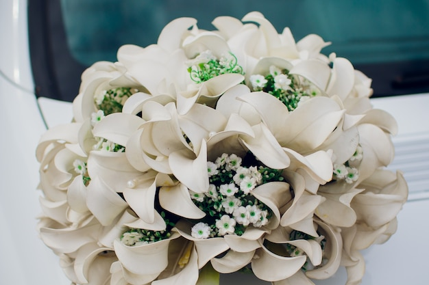 Primo piano di un bouquet da sposa in sordina con fiori rosa e viola.