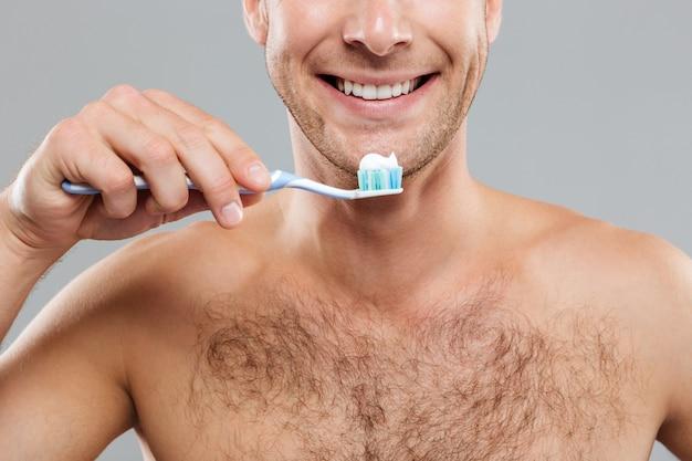 Primo piano del giovane allegro nudo che tiene spazzolino da denti con dentifricio