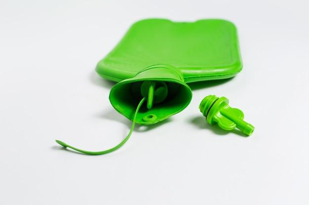 Primo piano del collo della bottiglia di acqua calda medica verde e del cappuccio isolati su fondo bianco.
