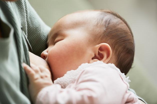 Primo piano del neonato che mangia latte prima di dormire mentre la madre la tiene in braccio