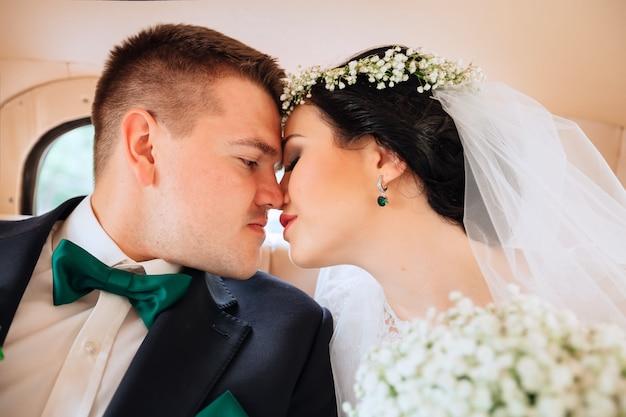 Primo piano di sposini seduti in macchina la sposa e lo sposo vogliono baciarsi