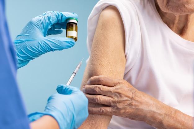 Infermiera del primo piano che fa l'iniezione del vaccino alla donna maggiore