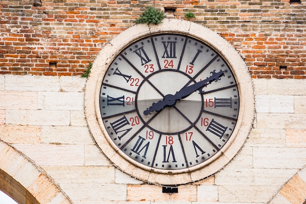 Primo piano del vecchio orologio della porta nuova medievale, porta della città vecchia di verona in italia