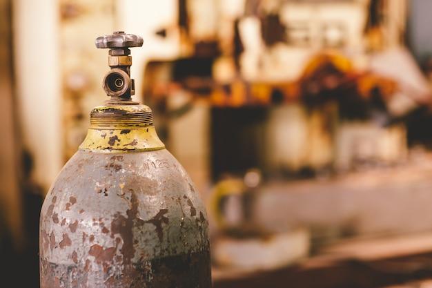 Vecchia valvola arrugginita del serbatoio di gas del primo piano, bombola a ossigeno di industria di non sicurezza del pericolo.