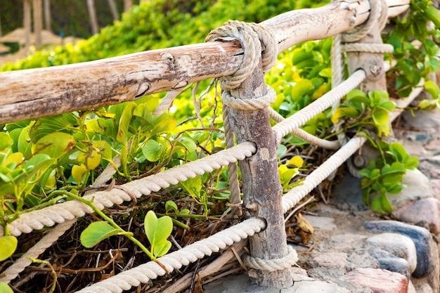 Primo piano della vecchia staccionata in legno ricoperta di corde di stoffa e vegetazione verde.
