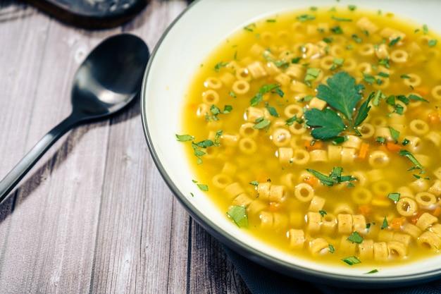Primo piano di una squisita zuppa di pollo e verdure con piccole tagliatelle e prezzemolo fatta in casa