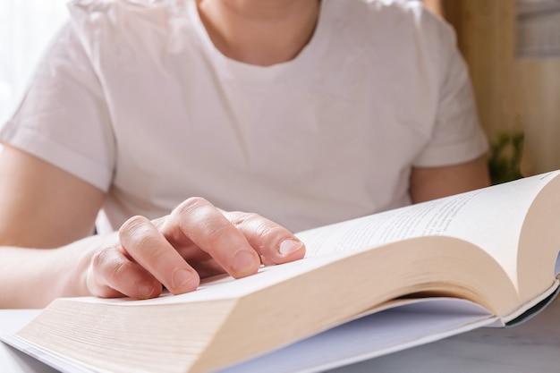 Primo piano del libro di carta spesso aperto nelle mani della donna.