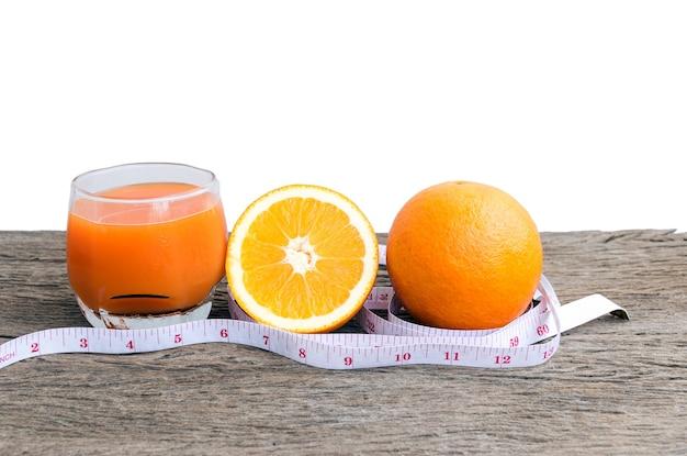 Primo piano di succo d'arancia e arance su un pavimento di legno