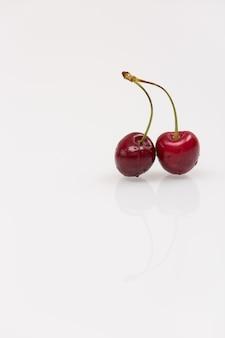 Primo piano delle ciliegie organiche su fondo di vetro bianco con la riflessione