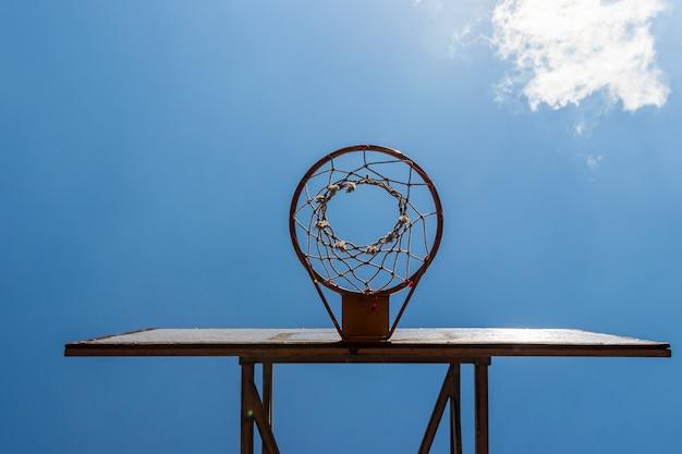 Cerchio e cielo blu di pallacanestro d'annata all'aperto del primo piano
