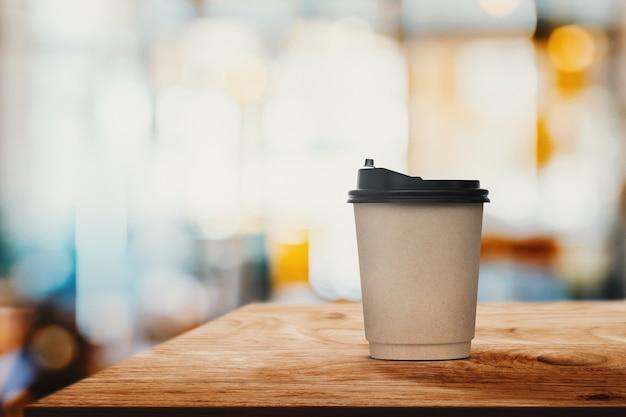 Tazza di caffè di carta del primo piano sulla tavola di legno con la caffetteria o il caffè interni della sfuocatura astratta per fondo