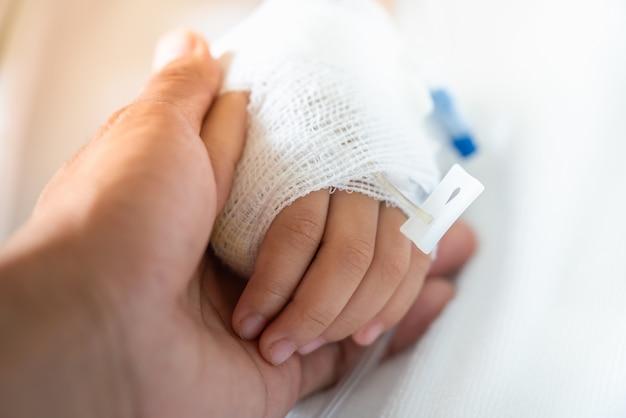 Genitore del primo piano che tiene la mano del bambino con la soluzione salina per dare incoraggiamento.