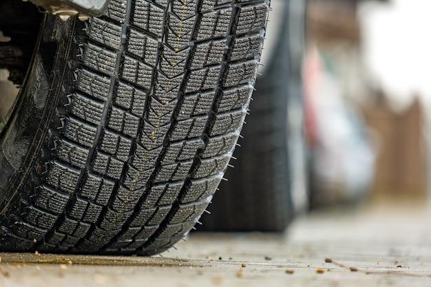 Primo piano della macchina parcheggiata su una strada di città con nuovi pneumatici invernali in gomma.