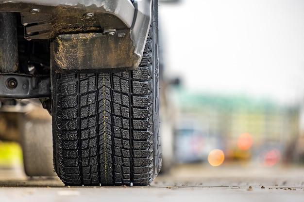Primo piano dell'auto parcheggiata su un lato della strada della città con nuovi pneumatici in gomma invernali.
