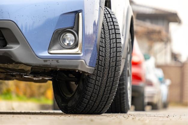 Primo piano dell'auto parcheggiata su una strada cittadina con nuovi pneumatici in gomma invernali.