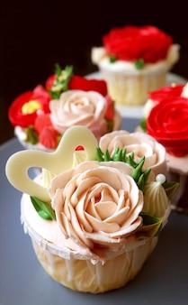 Cupcake glassa a forma di rosa rosa pastello del primo piano con un altro sullo sfondo