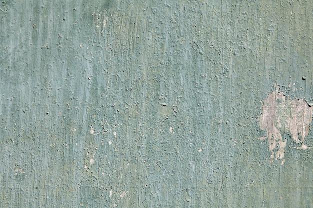 Primo piano peeling vernice verde chiaro sulla superficie del vecchio foglio di compensato incrinato, texture per sfondo.