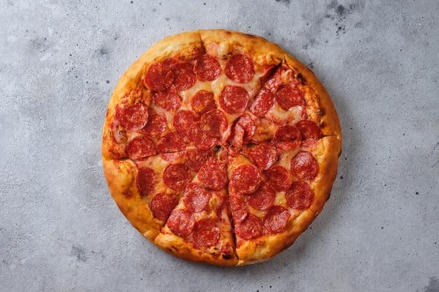 Un primo piano di una pizza ai peperoni pizza con salsiccia piccante salsa di pomodoro e mozzarella flat lay
