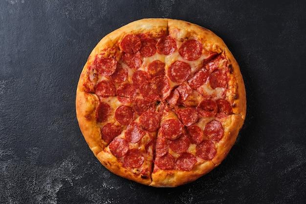 Un primo piano di una pizza ai peperoni pizza con salsa di pomodoro piccante e mozzarella