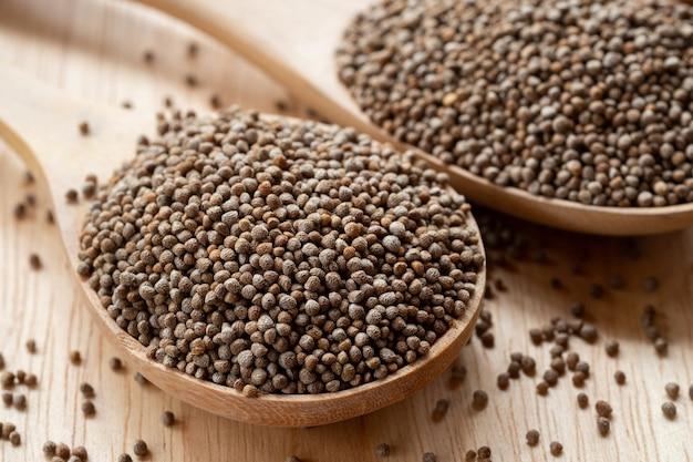 I semi di perilla del primo piano in un cucchiaio di legno sono grani che possono essere mangiati sia con semi che con foglie
