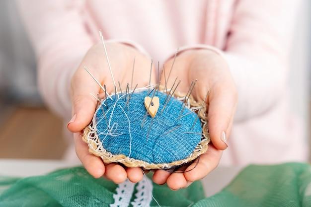 Primo piano della persona che tiene puntaspilli pieno di aghi