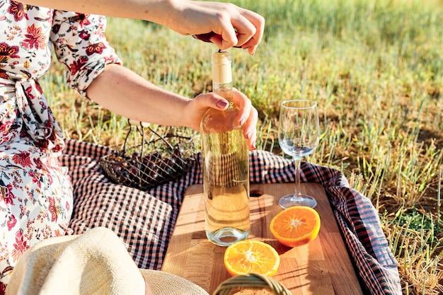 Primo piano di una persona che apre una bottiglia di vino durante un picnic