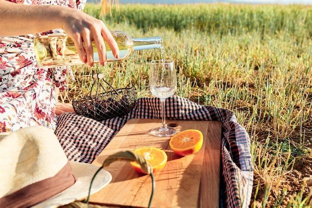 Primo piano di una persona che versa vino in un bicchiere durante un picnic