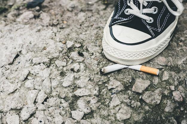 Primo piano del piede di una persona che indossa scarpe da ginnastica nere. scarpe che schiacciano un mozzicone di sigaretta sull'asfalto. smettere di fumare concetto