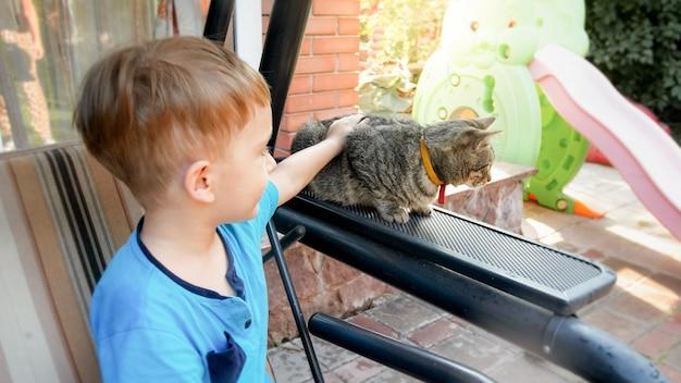 Primo piano di un adorabile bambino di 3 anni che accarezza un gatto grigio nel cortile di casa