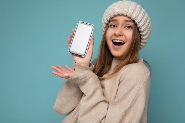 Foto del primo piano della giovane donna di bell'aspetto positiva stupita che indossa un maglione beige alla moda