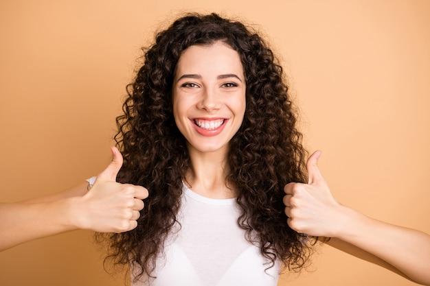 Foto del primo piano della signora di affari stupefacente che alza entrambi i pollici in su dentato raggiante sorridente consigliando novità indossare abbigliamento casual bianco isolato sfondo color pastello beige