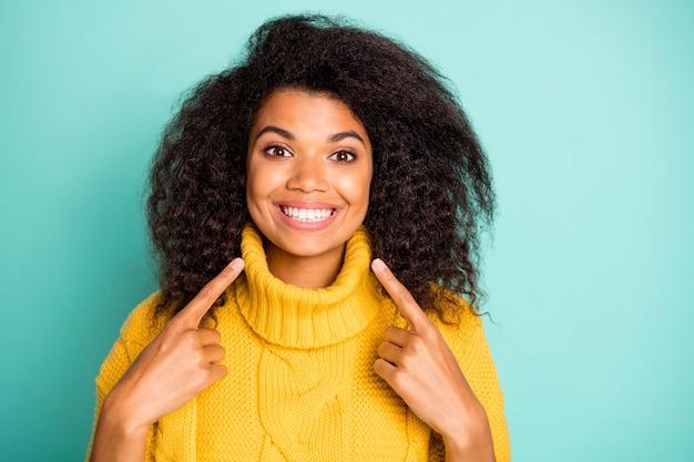 Foto del primo piano della signora riccia della pelle scura incredibile che indica le dita sui denti perfetti consigliando il dentista indossare pullover lavorato a maglia giallo isolato parete di colore verde acqua blu