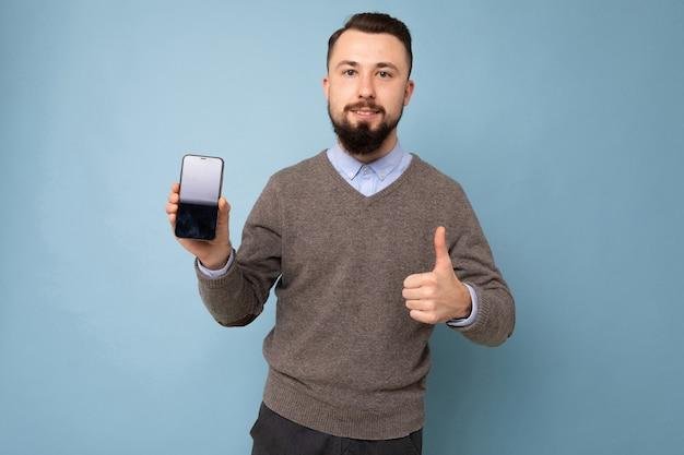 Foto del primo piano del ragazzo incredibile che tiene il telefono moderno mani vestito casual