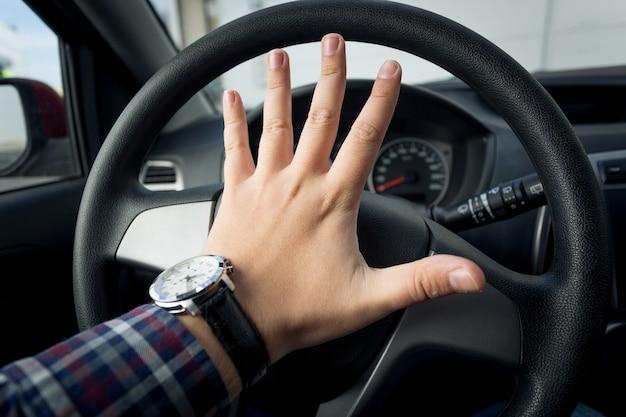 Primo piano dell'autista arrabbiato che suona il clacson nel traffico