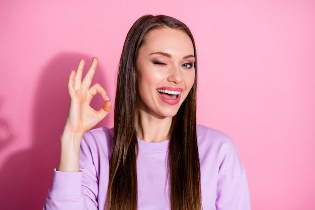 Foto del primo piano di attraente signora allegra spettacolo okey simbolo buon umore che esprime accordo lampeggiante occhio flirty fidanzata indossare maglione viola casual isolato sfondo rosa colore pastello