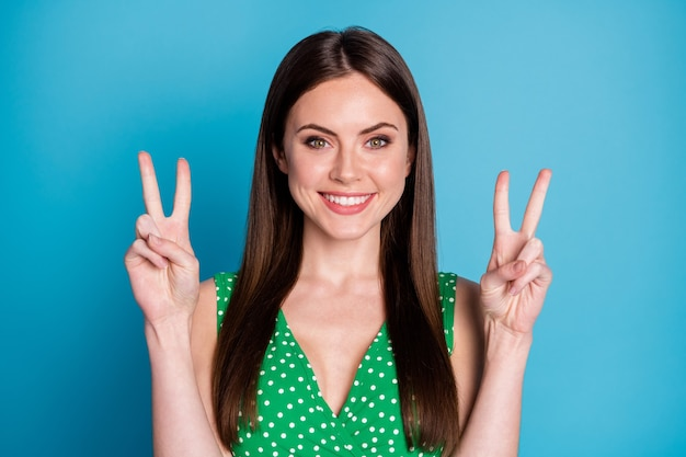 Foto del primo piano di attraente signora allegra divertente buon umore sorriso a trentadue denti affascinante carino da ragazzina che mostra i simboli del segno di v mani indossare canottiera punteggiata verde casual isolato sfondo di colore blu