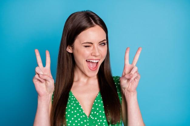 Foto del primo piano dell'attraente signora divertente buon umore affascinante aspetto carino che mostra i simboli del segno v mani civettuolo lampeggiante occhio indossare casual verde punteggiato canottiera isolato sfondo di colore blu