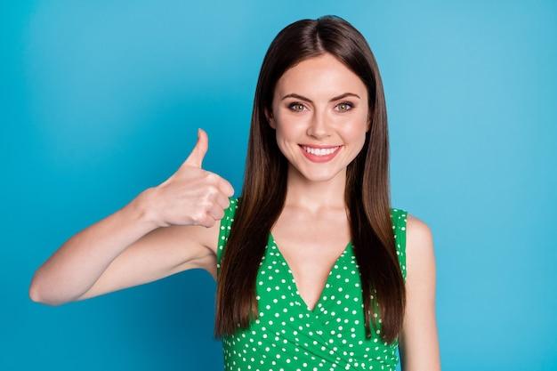 Primo piano della signora attraente buon umore alzare il braccio pollice dito su esprimendo accordo che approva la straordinaria qualità del prodotto indossare casual verde punteggiato canottiera isolato colore blu sfondo