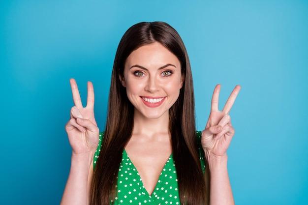 Foto del primo piano della signora attraente buon umore sorriso bianco a trentadue denti affascinante aspetto carino che mostra i simboli del segno v le mani indossano la canottiera punteggiata verde casual isolato sfondo di colore blu